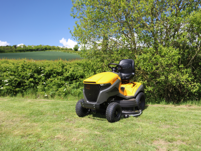 Loxston Groundcare ride on mower parked by hedge in field